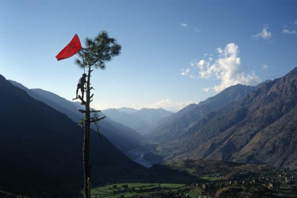Nabin Pun, a Maoist rebel soldier of the People's Liberation Army, raises the communist flag from a tree above the village of Rukumkot, Nepal, February 2005.