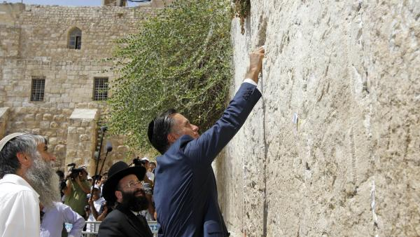 Republican presidential candidate Mitt Romney places a prayer note as he visits the Western Wall in Jerusalem on Sunday.
