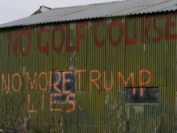 Graffiti on a shed captures the opposition to Donald Trump's planned golf course on the Aberdeenshire coastline in Scotland.