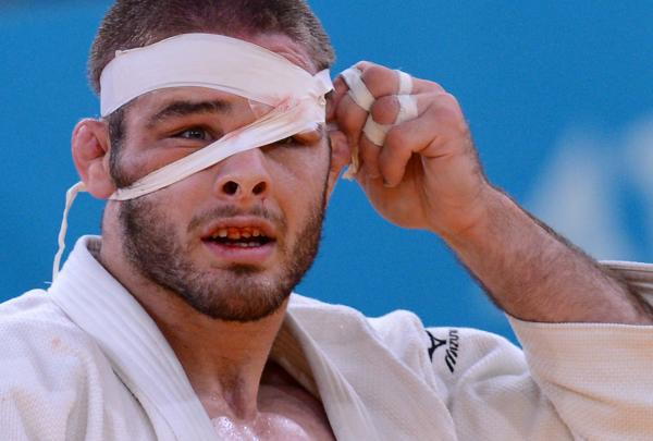 Travis Stevens adjusts his bandage as he competes with Germany's Ole Bischof during their men's -81kg judo contest semi-final match.