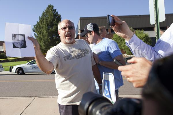 Tom Sullivan holds a picture of his son, Alex Sullivan, as he pleads with the media to help find him on July 20. Alex had gone to see a midnight showing of <em>The Dark Knight Rises</em> at the Aurora, Colo., theater where a shooter opened fire, killing 12 people and injuring 58 others.