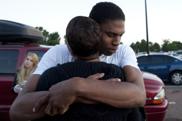 "Isaiah Bow hugs his mother, Shamecca Davis, after being questioned by police outside Gateway High School where he and other witnesses were brought after the shooting. After leaving the theater Bow went back in to find his girlfriend. ""I didn't want to leave her in there. But she's OK now,"" Bow said."