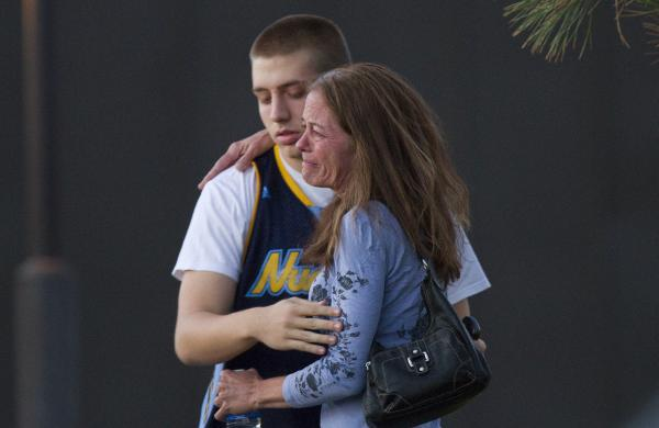 Eyewitness Jacob Stevens, 18, hugs his mother, Tammi Stevens, after being interviewed by police.
