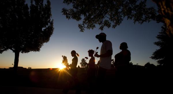 From left, Tylecia Amos, 14, Shatyra Amos, 15, Michael Walker, 17, and Mykia Walker, 16, carry flowers to a makeshift memorial across the street from the Century Theater parking lot on July 21. Walker was a classmate of AJ Boik, who was killed in the shooting.