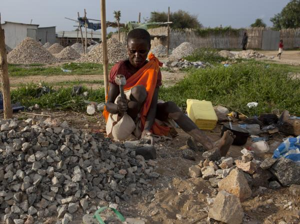 A woman pounds rocks for a few dollars a day in Juba, South Sudan.