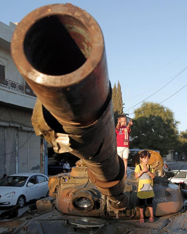 In Aleppo, Syria, on Thursday: Children climb on an abandoned Syrian army tank.