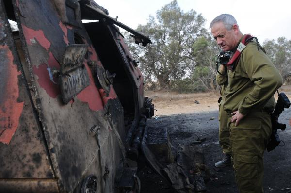 A photo released by the Israeli army shows Israeli chief of staff Lieutenant General Benny Gantz inspecting a burnt vehicle near the Kerem Shalom border crossing after unidentified gunmen crossed into Israel from Egypt.