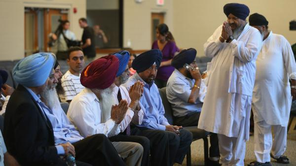 Members of the Milwaukee-area Sikh community gather Monday in Oak Creek, Wis., to learn more information about a shooting spree that left six people dead. Sikhs have faced a number of attacks in the U.S. in recent years.