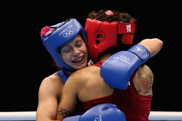 Sofya Ochigava (in blue) of Russia hugs Adriana Araujo of Brazil after their bout during the Women's Light Boxing semifinals on Day 12 of the London 2012 Olympic Games. Ochigava won the bout.
