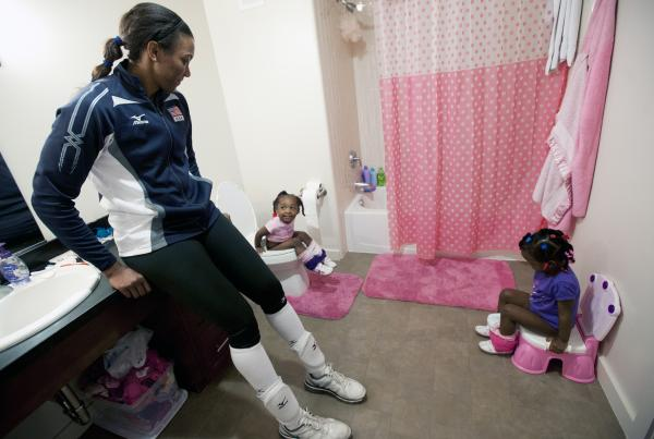 Danielle Scott-Arruda helps her grandniece Madison (left) and daughter Julianne in the bathroom. Scott-Arruda is a volleyball player on the U.S. Olympic team.
