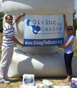 Tim Bair and Theresa Hamilton hoist a Giving the Basics banner.