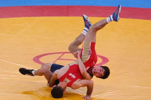 Dzhamal Otarsultanov of Russia (in red) and Vladimer Khinchegashvili of Georgia wrestle during the men's freestyle 55-kilogram gold medal match. Otarsultanov won the event.