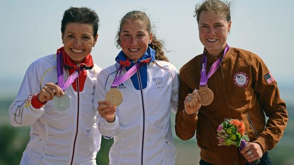 France's gold medalist Julie Bresset (center), Germany's silver medalist Sabine Spitz (left) and U.S. bronze medalist Georgia Gould stand on the podium of the women's cycling cross-country mountain bike event in Benfleet, England.