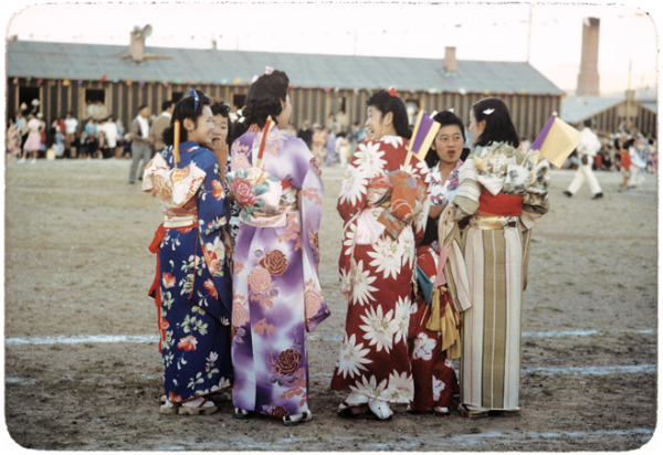 Young women wearing kimonos chat during an Obon celebration honoring ancestors at the Heart Mountain Relocation Center in Wyoming.