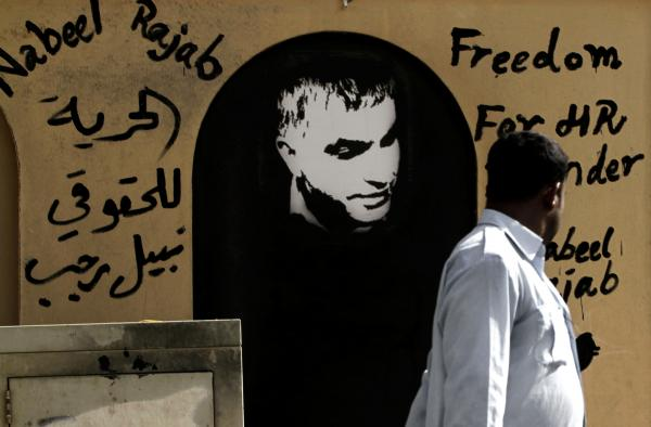 "A man walks past a picture of human rights defender Nabeel Rajab and Arabic that reads, ""freedom to human rights defender Nabeel Rajab."""