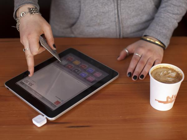 A barista processes a customer's payment using Square, a device that turns a mobile device into a card swiper. More businesses are using the devices to simplify credit card payments. Others are embracing technology that allows consumers to pay with their cellphones.