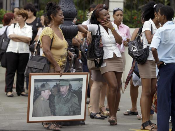 People, one holding an image of Cuba's President Raul Castro  and his brother Fidel Castro, wait in line at a bus stop in Havana last month.