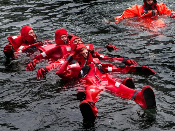 Crew members of a scallop boat float in their survival suits during a drill in Point Judith, R.I.