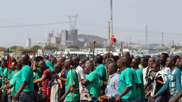 Mine workers attend a memorial service in South Africa Thursday, Aug. 23, for miners killed last week by police officers.