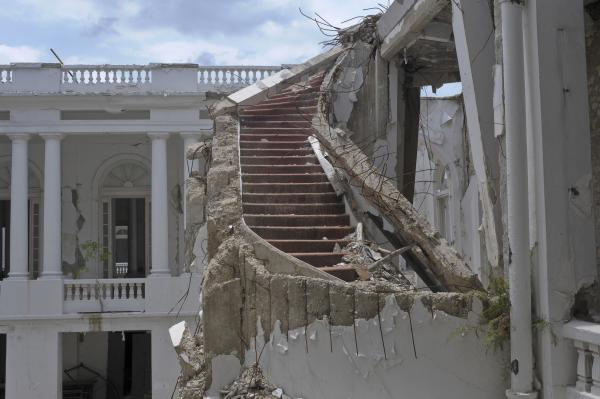 "A ruined staircase is seen in the collapsed National Palace. Parker described it as ""a staircase of grandeur."""