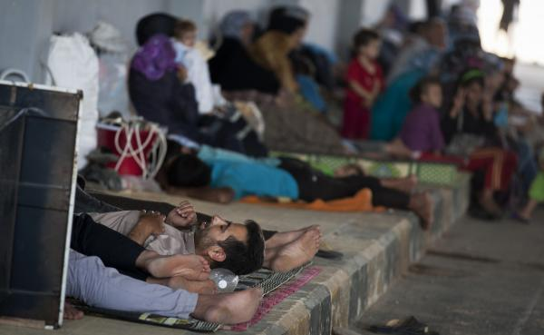 Syrians wait on the Syrian side of the border to be admitted to Turkey on Wednesday, Aug. 15.