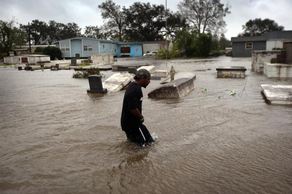 Errol Ragas walks past a cemetery to recover dry blankets from his home as rising waters from Hurricane Isaac flood the neighborhood  of Oakville in Plaquemines Parish, Louisiana.