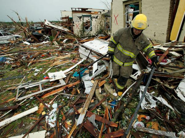 A firefighter searches a home Monday, May 23, 2011, that was destroyed  by a tornado in Joplin, Mo.