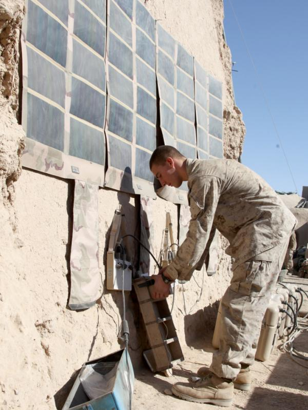 In this photo released by the U.S. Marines and taken in December 2010, Lance Cpl. Dakota Hicks, from Laharpe, Ill., connects a radio battery to a portable solar panel communication system in Sangin District, in Afghanistan.The U.S. military is trying to wean itself off reliance on fossil fuels by employing solar energy and biofuels, among other measures.
