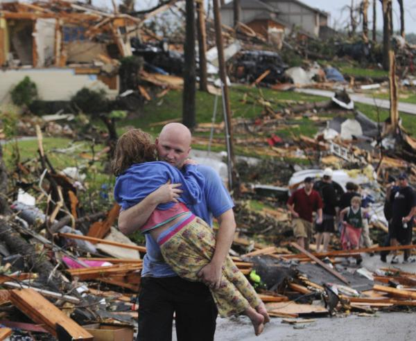 A man carries a young girl who was rescued after being trapped with her mother in their home after a tornado hit Joplin.