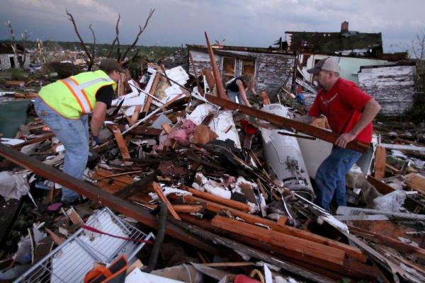 Volunteer firefighters William Jackson (from left) and Ashley Martin of Oklahoma and Johnny Ward of Joplin look through the wreckage of a home where it was feared a pregnant woman was trapped.