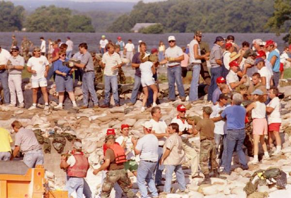 Hundreds of residents in Prairie Du Rocher, Ill., pass sandbags along a levee in a last-ditch attempt to save the town, 1993.