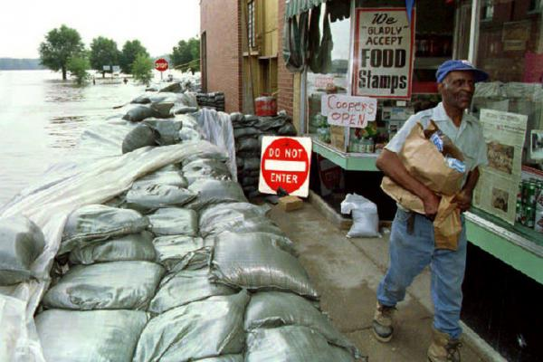 Milton McPike gathered supplies from Cooper's grocery store in Hannibal, Mo., as rising water from the Mississippi River threatened to surround it, 1993.
