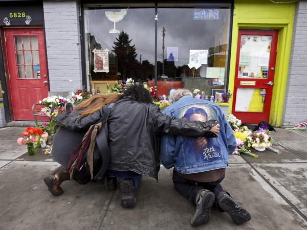 Left to right: Karen Eides, Tim Torres and David Gordon embrace as they kneel in front of a makeshift memorial outside the cafe in Seattle where a gunman killed four people.