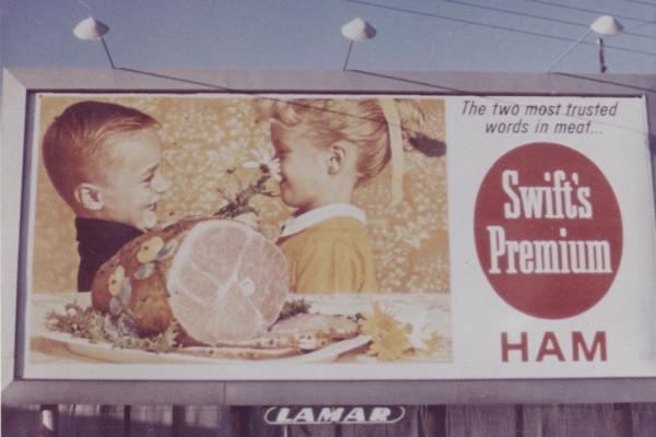 The Swift's Premium ham is front and center in the depiction of family holiday fun in this vintage billboard.