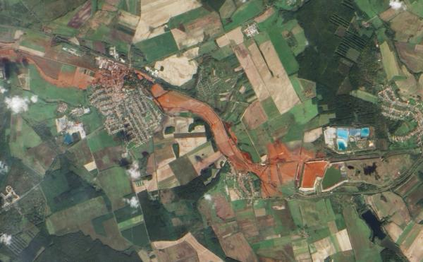 Aerial view of the toxic red sludge flowing from a breached waste reservoir (diamond shape at right) through the villages of Kolontar and Devecser.