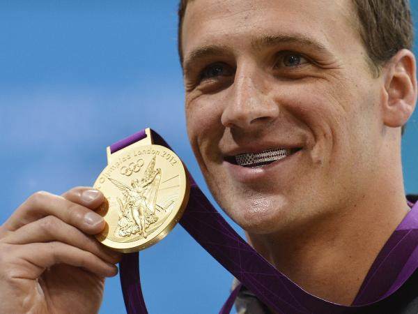 Ryan Lochte smiles on the podium with his new gold medal after winning the men's 400m individual medley in London Saturday. Lochte is wearing a dental accessory known as grillz, in the shape of the American flag.