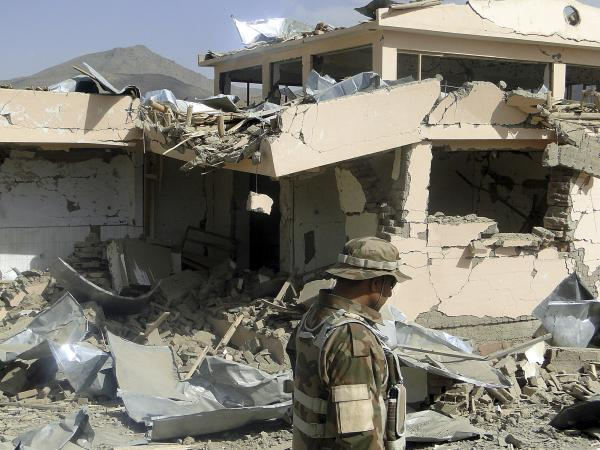 A security official looks at rubble of a building destroyed during a twin suicide bomb attack in Wardak province, Afghanistan, on Saturday.