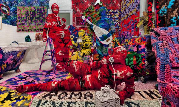 "<em>Knitting Is for Pus****</em> is a work by <a href=""http://40u40.beancreative.com/artist28.html"">crochet sculptor Olek</a>. He has created an entire apartment blanketed in brightly colored, crocheted camouflage."