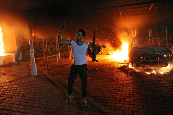 An armed man waves his rifle as buildings and cars are engulfed in flames after being set on fire inside the US consulate compound in Benghazi late on Tuesday.