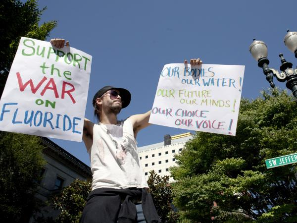 Demonstrator China Starshine holds up signs outside of City Hall in Portland last week.