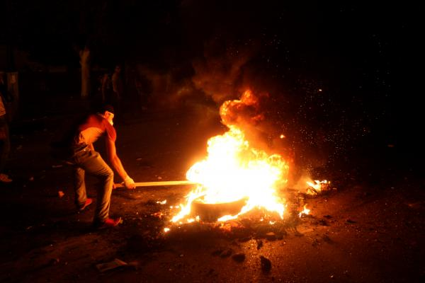 A protester sets a tire on fire during clashes with police in front of the U.S. Embassy in Cairo.