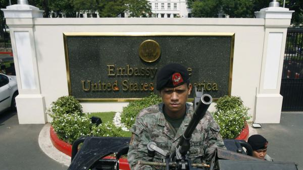 An armed police officer stood guard on a machine gun-mounted jeep outside the U.S. embassy in Manila, Philippines, amid warnings of a terrorist plot June 6, 2007.