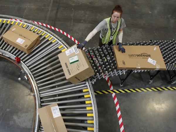 An Amazon worker sorts packages at a fulfillment center in Goodyear, Ariz.