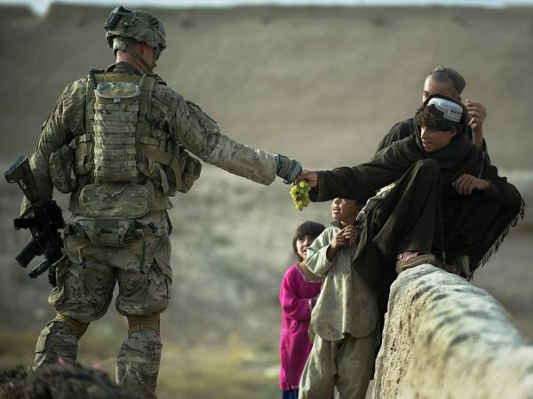 A U.S. soldier shares grapes with Afghan boys in the southern province of Kandahar on Wednesday.