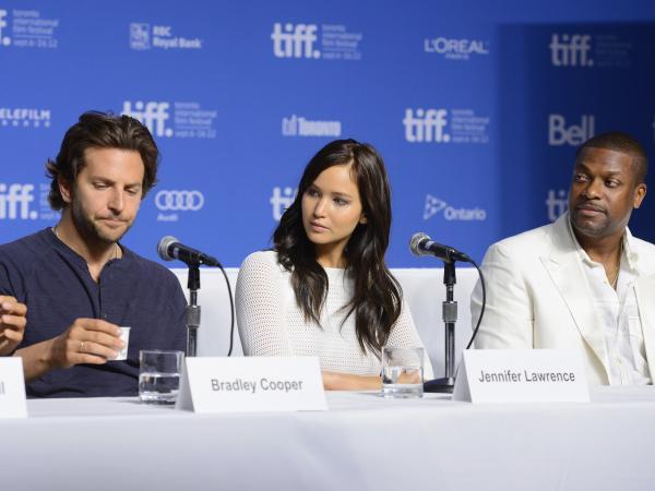 Actors Bradley Cooper (left), Jennifer Lawrence and Chris Tucker speak onstage at <em>Silver Linings Playbook</em> press conference Sept. 9 during the 2012 Toronto International Film Festival.