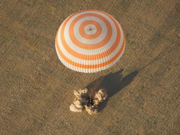 The capsule lands, after its braking engines ease its final meter of descent.