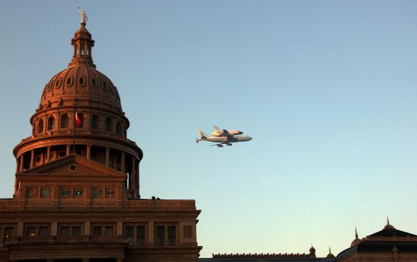 Space Shuttle Endeavour sits atop the shuttle aircraft carrier, flies over downtown Austin, Texas early Thursday.