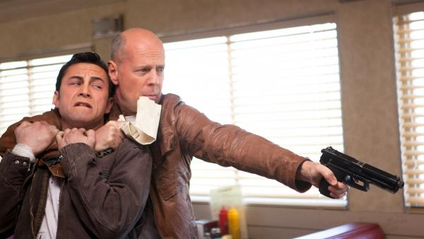 Joseph Gordon-Levitt and Bruce Willis star as present and future versions of the same man in <em>Looper</em>.