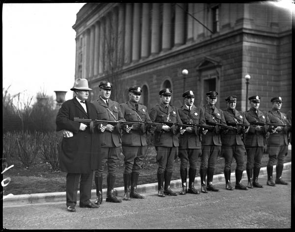 The Illinois State Police purchased new Thompson submachine guns in 1931 to help them face the threats of the day, which included bootleggers and labor unrest that frequently turned violent. The guns were issued to every sergeant in each police district throughout the state. Capt. Carr (left) posed with his officers and their guns in front of the Centennial Building, February 1931.