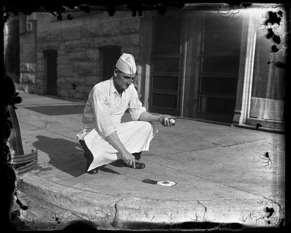 T.M. Travis, owner of Travis Cafeteria at 624 E. Capitol Ave., tries to prove, or disprove, the belief that it is sometimes hot enough to fry an egg on the sidewalk in July 1930. Despite it being 115 degrees on the concrete, the experiment did not work.